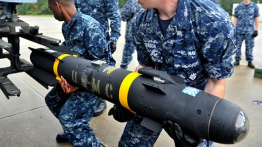 USMC Hellfire missile being loaded by US Navy sailors on an aircraft mount. Note the size of the missile requires two men to hold it up.